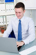 angestellter arbeitet am laptop im büro