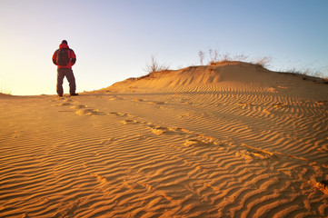Sandy desert and man in winter clothes standing at a dune top