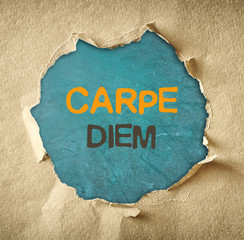 the phrase carpe diem written over chalkboard through hole