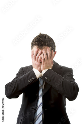 stressed business man covering his face with his hands