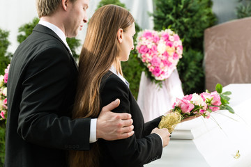 Leute auf Beerdigung mit Sarg