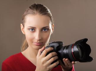 Beautiful young woman with camera. isolated on grey background.
