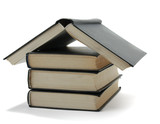 House made with books piled on white background.