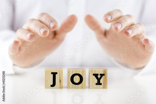 Mans hands cupped over the word Joy