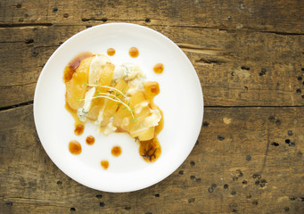 Baked pear with caramel, gorgonzola cheese and thyme on wooden