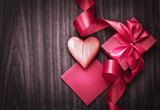 REd Holidays gift and heart on wooden background/ Valentines day