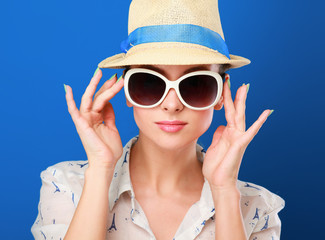 Young woman in hat and sunglasses , isolated on blue background.