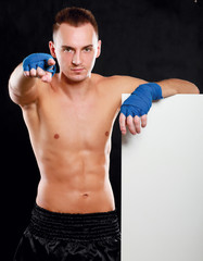 Young handsome boxer man standing near board and pointing at you