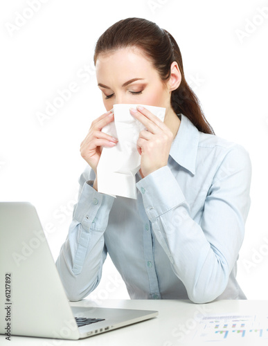 Portrait of a sick young business woman blowing her nose