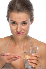 Doubting young woman with pill and glass of water