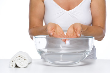 Closeup on happy woman washing hands in glass bowl with water