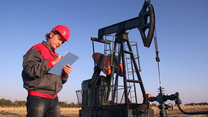 Engineer writing on clipboard beside the oil pump