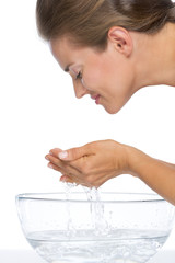 Young woman washing face in glass bowl with water