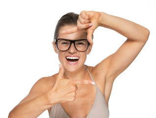 Happy young woman in eyeglasses framing with hands