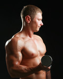 Handsome muscular man working out with dumbbells.