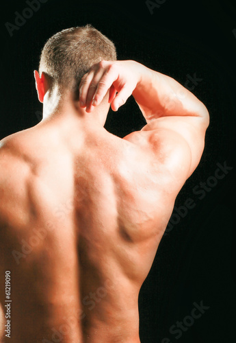 Muscular man with back neck ache isolated on black background.