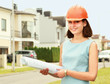 Female architect at a construction standing with folder