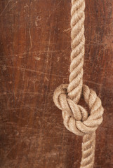Rope with Reef Knot on Wood Texture Background