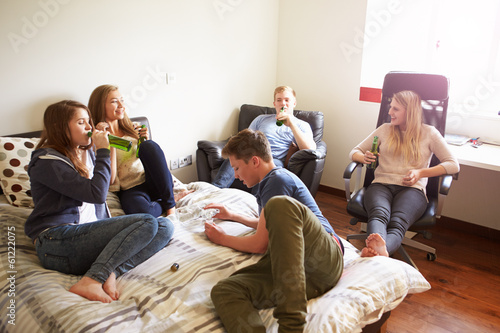 Group Of Teenagers Drinking Alcohol In Bedroom