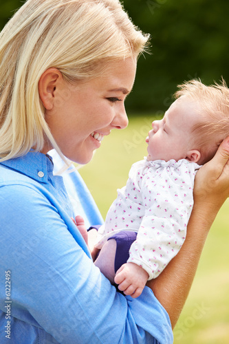 Loving Mother Holding Baby Daughter In Garden