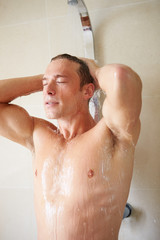 Man Taking A Shower In Bathroom