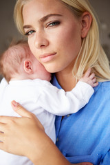 Depressed Mother Cuddling Newborn Baby