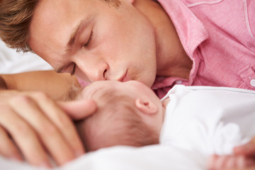 Father Kissing Baby Girl As They Lie In Bed Together