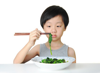Young boy eating vegetables