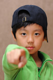 Cute boy with black cap pointing with index finger
