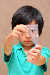 Asian schoolboy holding a set square (triangle)