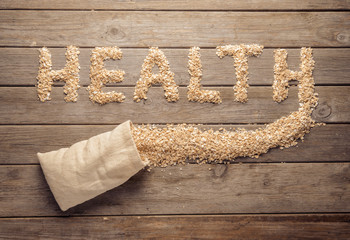 Health word shape of oatmeal flakes on a wooden table