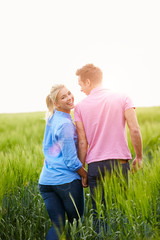 Romantic Couple Walking In Field Holding Hands