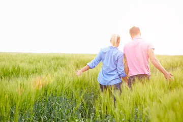 Rear View Of Romantic Couple Walking In Field Holding Hands