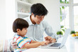 Asian Father Helping Son To Use Laptop At Home