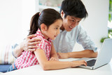 Asian Father Helping Daughter To Use Laptop At Home