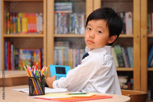 Schoolboy distracted by game machine during homework time