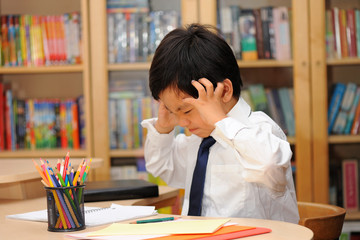 Frustrated Asian schoolboy in school uniform