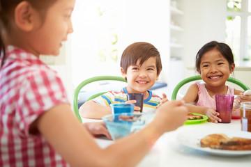 Three Asian Children Having Breakfast Together In Kitchen
