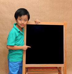 Boy standing next to blackboard pointing with his index finger
