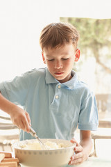 boy makes a cake in kitchen