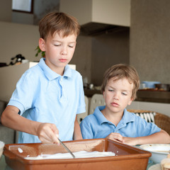 Two boy makes a cake in kitchen