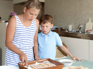 Two kids makes cake in kitchen