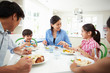 Asian Family Sitting At Table Eating Meal Together