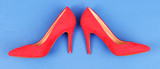 Beautiful red female shoes, on blue background