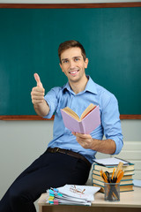 Young teacher sitting with book on desk in school classroom