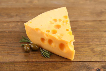 Piece of cheese with green olives, on wooden background