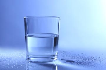 Water in  glass, on dark blue background