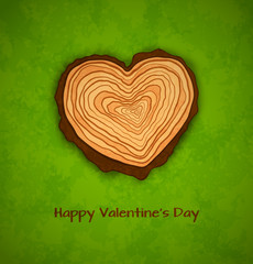 Wooden heart on green background
