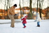 Father and his daughters having fun on winter day