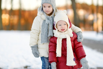 Two little sisters having fun on winter day